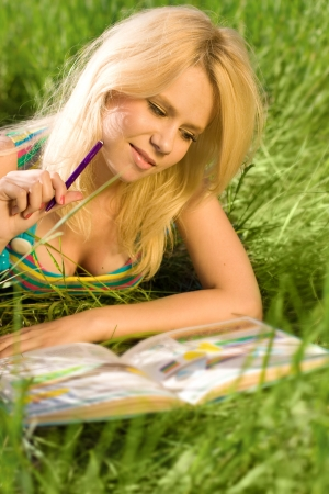 Blonde young girl reading on a lawn photo