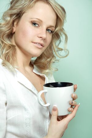 Young girl with a cup of hot beverage photo