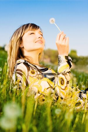 Attractive young girl relaxing on a meadow, holding dandelion flower in her hand photo