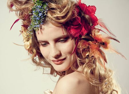 Stylized summer portrait of a young beautiful woman with flowers in her hair photo