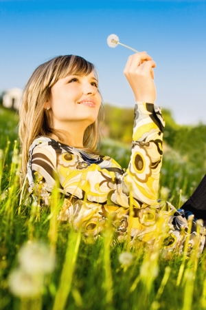 A lovely young girl relaxing on a meadow, holding dandelion flower in her hand photo