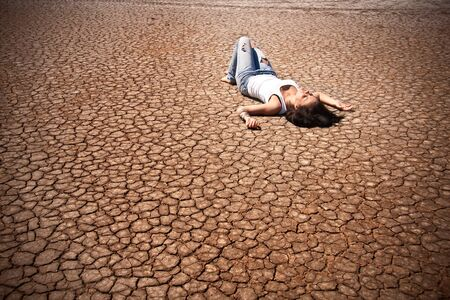 Young woman lying in the middle of a desert. photo