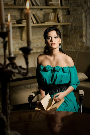 Beautiful young brunette woman reading a book. Retro stylization. photo