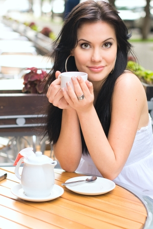 Young woman drinking tea in a caffe outdoors