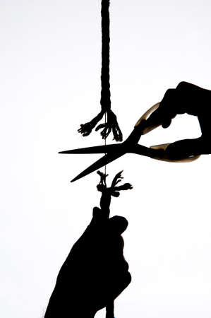 A hand holds a rope, scissors cuts the same string