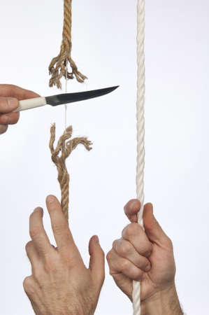 A hand holds a rope, a knife cuts the same string Stock Photo - 12881937