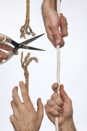 A hand holds a rope, scissors cuts the same string Stock Photo - 12881908