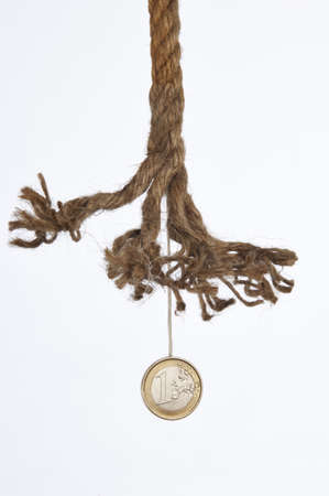 One euro coin hanging by a frayed rope photo