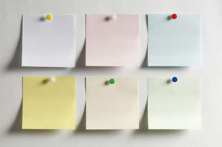 Blank paper, hanging on the wall with a colored pushpin