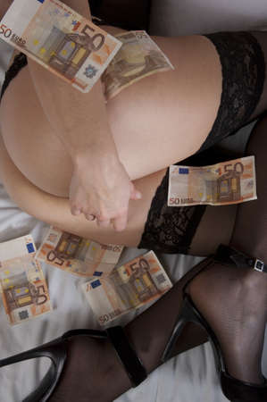 Some fifty euro banknotes were on thighs and buttocks and inserted in the stockings of a girl wearing lingerie and high heels lying on the bed Stock Photo - 12881891