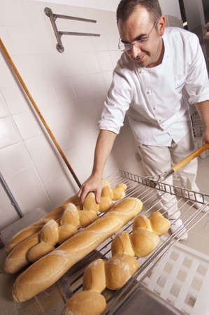 Baker keeps the bread fresh from the oven Stok Fotoğraf - 12881780