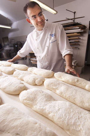 Baker makes the bread kneaded in the oven Stock Photo