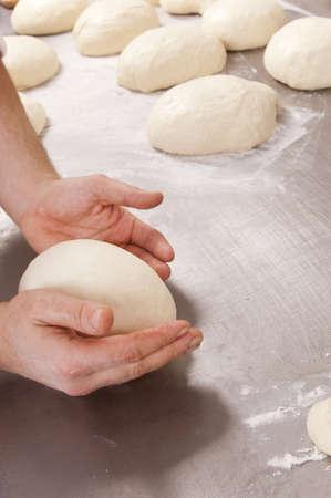 Baker kneads the flour on a shelf, to make bread