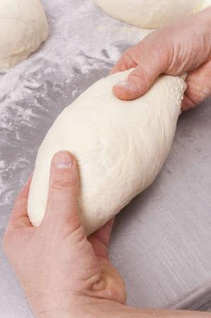 Baker kneads the flour on a shelf, to make bread photo