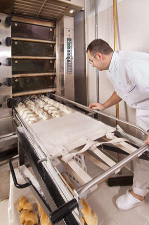 Baker makes the bread kneaded in the oven Stock Photo - 12881779
