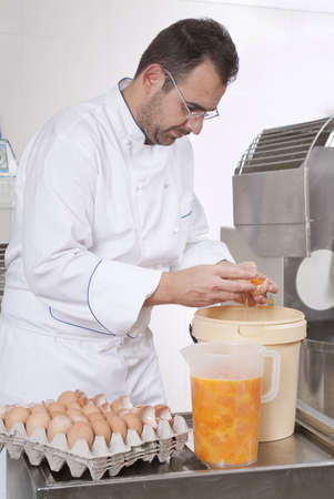 commercial kitchen: Pastry Chef prepares eggs dividing the Youk, put it in a jar