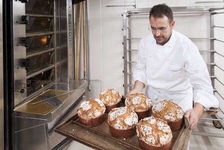 Pastry Chef, takes away the panettone from the oven freshly cooked photo
