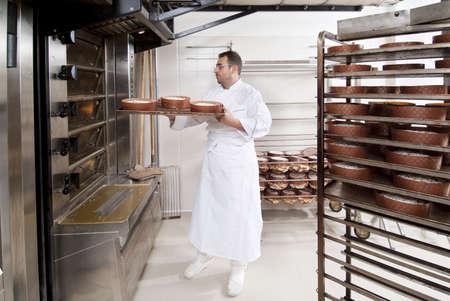 panettiere: Chef Pastry, toglie il panettone dal forno cucinato Archivio Fotografico