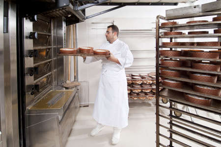bakery oven: Pastry Chef, takes away the panettone from the oven freshly cooked