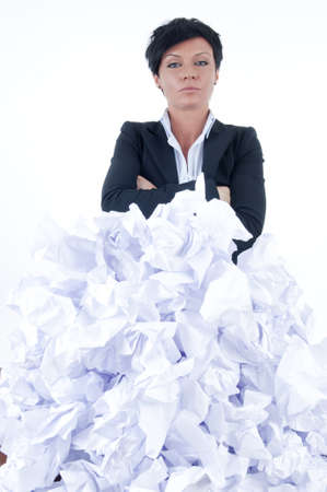 imploring: business woman behind a pile of crumpled paper
