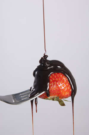 Liquid chocolate, falls on a strawberry stuck in a fork photo