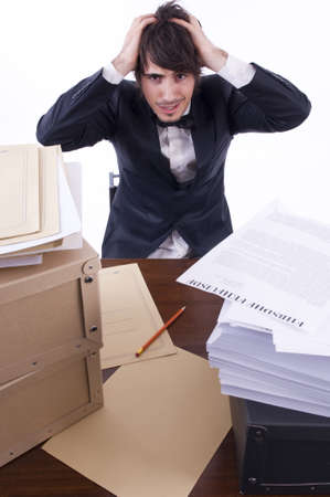 excess: Businessman stressed in his office, many documents on the desk