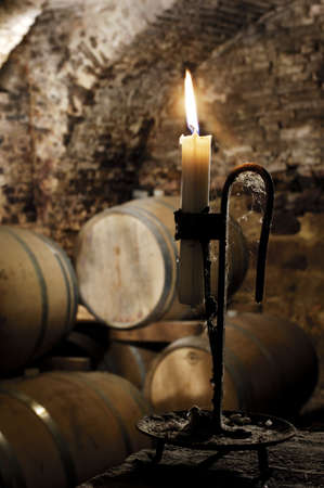 Old candlestick with lighted candle in a cellar where there are  barrels wine Stok Fotoğraf