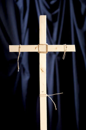 Catholic cross in front of a curtain of black cloth photo