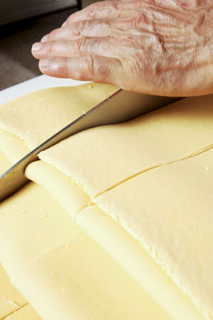 technical department: Man with knife cuts sheets of fresh pasta