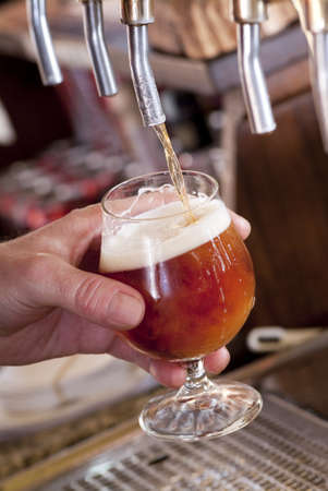 Brewer fills a glass with beer on tap photo
