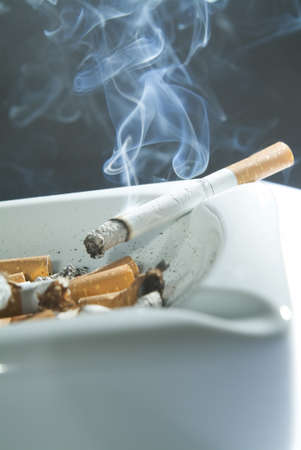 cigarette left burning on the edge of an ashtray Stock Photo