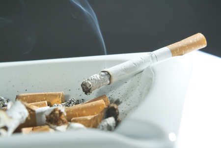 ashtray: cigarette left burning on the edge of an ashtray Stock Photo