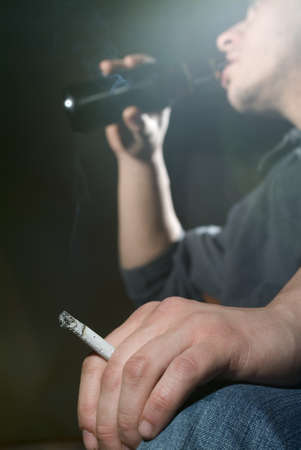 smoker: Man drinking from a bottle and holding a cigarette between his fingers