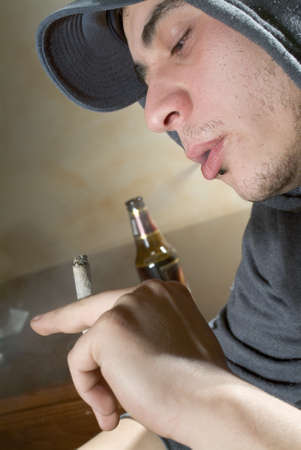 joven fumando: Boy prepara y se fuma un cigarrillo en un interior
