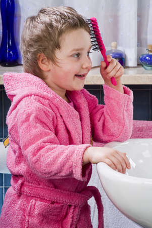 Little girl combing her hair with a brush in the bathroom photo