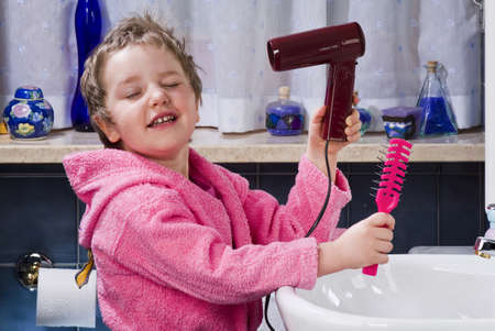 Girl dries her hair with a hairdryer in the bathroom