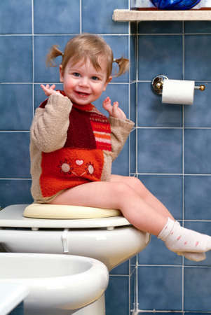 Little girl on the toilet that makes funny faces Stock Photo - 13203351