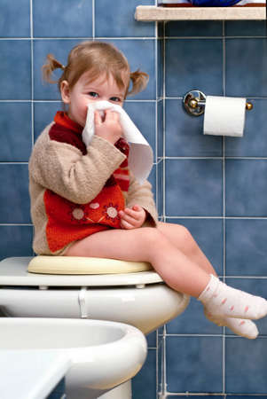 Little girl on the toilet that cleans the nose photo