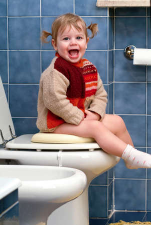 Little girl on the toilet that makes funny faces photo