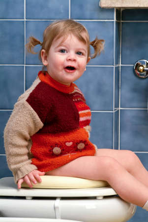 Little girl on the toilet that makes funny faces Stock Photo - 13203309