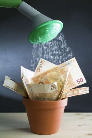 With a bucket of water, washed down by fifty euro banknotes in a orange vase Stock Photo - 13235342