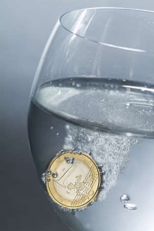 A one euro coin in a glass full of water as an effervescent aspirin Stock Photo