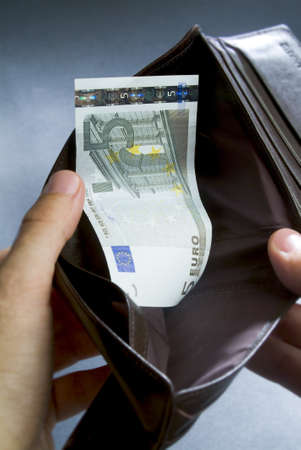 vacant: hands looking for in a wallet which has only five euro inside Stock Photo