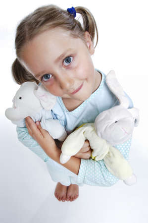 Girls in pajamas with toys in her arms makes the face of an angel photo