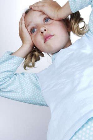 facial gestures: Las ni�as en pijama asombrados pone las manos en la cabeza Foto de archivo