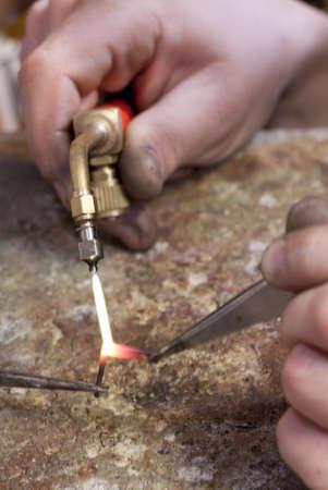 Welder welding a piece of metal is held with tweezers Stock Photo
