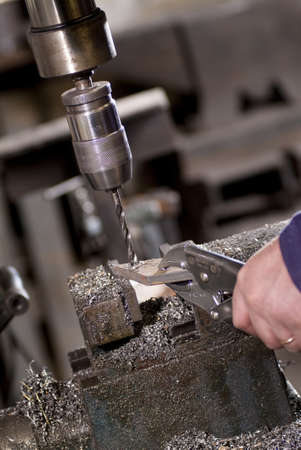 machinist: Worker drilling a piece of iron that held with forceps Stock Photo