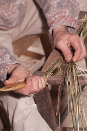 Carpenter weaves straw for repair of old chairs photo