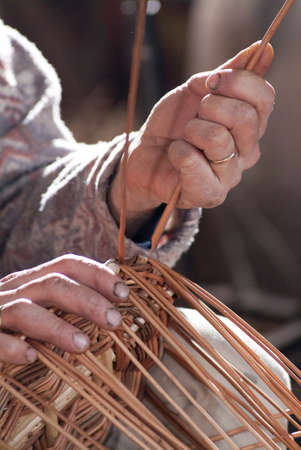 Carpenter weaves the rush to make a basket Stock Photo