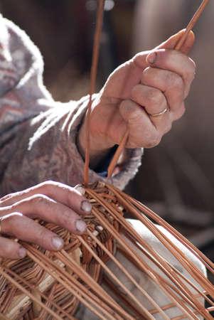Carpenter weaves the rush to make a basket 免版税图像